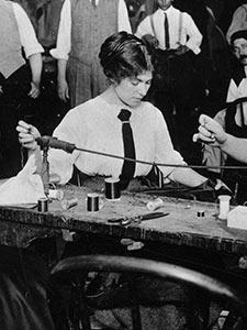 WORKERS AT A SMALL BENCH HAND FINISH GARMENTS WHILE MANAGERS LOOK ON