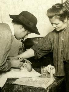 A VISITING NURSE FROM HENRY STREET SETTLEMENT TREATS AN INFANT IN A TENEMENT APARTMENTv