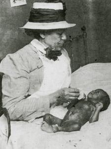 AFRICAN-AMERICAN NURSE FROM HENRY STREET SETTLEMENT VISITS MOTHER AND BABY, CA. 1910
